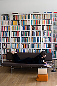Germany, Berlin, young woman reading in living room