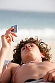 Cape Verde Peninsula, Sal, Santa Maria beach, teen boy with Ipode