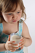 Little girl drinking glass of milk, studio