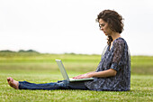 Young woman sitting in grass, using laptop computer