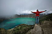 Man With Outstretched Arms Standing at Top of Large Crater Filled With Water, Quilatoa, Ecuador
