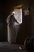Gnawa Musician in White Robe Looking out Window, Khemlia, Morocco