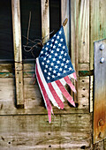 Tattered American Flag Tied to Weathered Door