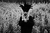 Girl With Long Blonde Hair Wearing Feathered Mask in Field of Wildflowers