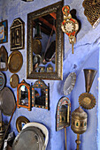 Mirror and silver plates on a blue wall and door of a shop in a narrow alley at Chefchaouen, Riff mountains, Morocco, Africa