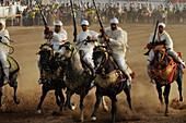 Men on horseback carrying guns, Fantasia festival for the Moussem of Moulay Abdallah near el-Jadida, Atlantic Coast, Morocco, Africa