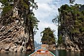 Long tail boat between limestone rocks on the Khao Sok National Park Reservoir Lake, Khao Sok National Park, Andaman Sea, Thailand