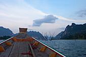 Longtailboot und Karstfelsen am Abend auf dem Stausee des Khao Sok Nationalparks, Khao Sok Nationalpark, Andamanensee, Thailand