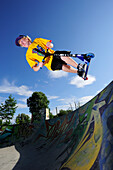 Young man performing jump with scooter, skatepark, Munich, Upper Bavaria, Germany