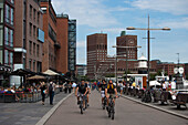 Cyclists cycling along the promenade, Oslo Radhus, city hall in the background, Oslo, Oslo, Norway