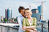 Couple embracing, Elbe Philharmonic Hall construction site in background, HafenCity, Hamburg, Germany