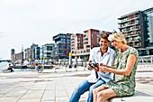Couple with digital camera at Magellan-Terraces, HafenCity, Hamburg, Germany