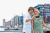 Couple taking photograph of themselves, Magellan-Terraces, HafenCity, Hamburg, Germany