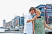 Paar fotografiert sich mit einem Handy, Magellan-Terrassen, HafenCity, Hamburg, Deutschland