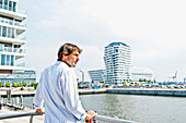 Mid adult man looking over Strandkai, Marco-Polo-Tower in background, HafenCity, Hamburg, Germany