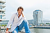 Mid adult man smiling at camera, Marco-Polo Tower in background, HafenCity, Hamburg, Germany