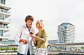 Smiling couple with mobile phone leaning against balustrade, Marco-Polo-Tower in background, HafenCity, Hamburg, Germany