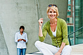 Woman sitting on step, man with mobile phone standing in background, HafenCity, Hamburg, Germany