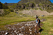 Female hiker crossing river near Lac Roumassot, Ossau Valley, French Pyrenees, Pyrenees-Atlantiques, Aquitaine, France