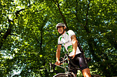 Bicycle racer under deciduous trees, Bergisches Land, North Rhine-Westphalia, Germany
