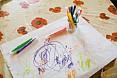Child's drawing and color pens on table