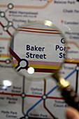 'Magnifying glass over London underground map, examining ''Baker Street'' station'