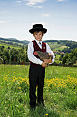 Boy holding a chicken wearing traditional Black Forest clothes, Gottertal, Baden-Wurttemberg, Germany