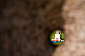 Woman enjoys yoga and meditation, seen through hole in rock sculpture, near Klaipeda, Klaipedos, Lithuania