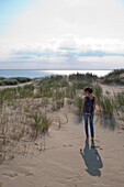 Woman strolls along sand dune on Curonian Spit [MR], near Klaipeda, Klaipedos, Lithuania