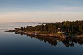 Leuchtturm und idyllisch gelegenes Haus in den Stockholmer Schären, Blick von Kreuzfahrtschiff MS Astor, Transocean Kreuzfahrten, während einer Kreuzfahrt durch die Ostsee, nahe Stockholm, Schweden, Europa