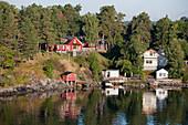 Idyllisch gelegene Häuser in den Stockholmer Schären, Blick von Kreuzfahrtschiff MS Astor, Transocean Kreuzfahrten, während einer Kreuzfahrt durch die Ostsee, nahe Stockholm, Schweden, Europa
