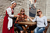 Waitress in medieval costume and tourists with mugs of beer at Olde Hansa restaurant in Town Hall Square (Raekoja Plats), Tallinn, Harjumaa, Estonia