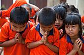 School children in uniform welcome visitors with wai greeting, near Kanchanaburi, Thailand
