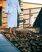 Hotel guests in bathrobes walking over forest floor, outdoor sauna area, Vigiljoch, Lana, Trentino-Alto Adige/Suedtirol, Italy