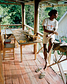Field guide and jewellery maker Silvin Fanchette on the terrasse of his typical old island style house in La Passe, La Digue and Inner Islands, Republic of Seychelles, Indian Ocean