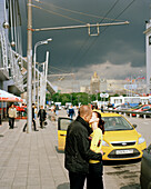 Kissing couple in front of a taxi at Jevropeski Plaza, Moscow, Russia, Europe