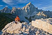 Young man sitting on a rock enjoying the view, Dachstein, Salzburg, Austria, Europe