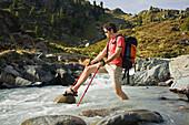 Young man crossing a stream, Oetztal Alps, Tyrol, Austria, Europe