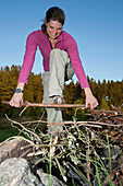 Young woman breaking firewood, laughing, lake Ottenstein, Lower Austria, Austria, Europe