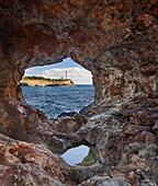View through hole in a rock onto lighthouse of Portocolom, Punta de s'Homonet, East Coast, Mallorca, Spain, Europe