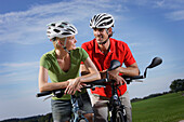 Cyclists leaning on handlebar, Lake Starnberg, Bavaria, Germany