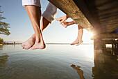 Family sitting on a jetty, close-up feet, Lake Starnberg, Bavaria, Germany