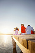 Family sitting on a jetty at lake Starnberg, Bavaria, Germany