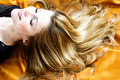Portrait of a young woman lying, long hair on yellow textil fabric
