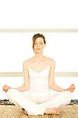 Young woman sitting cross-legged, yoga attitude, shut eyes