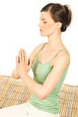 Woman meditating, shut eyes, folded hands