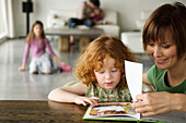 Woman and little girl reading a children's book