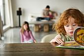 Little girl reading children's book, family in the background