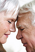 Senior couple face to face, eyes shut, close-up