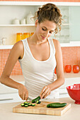 Woman chopping cucumbers in the kitchen